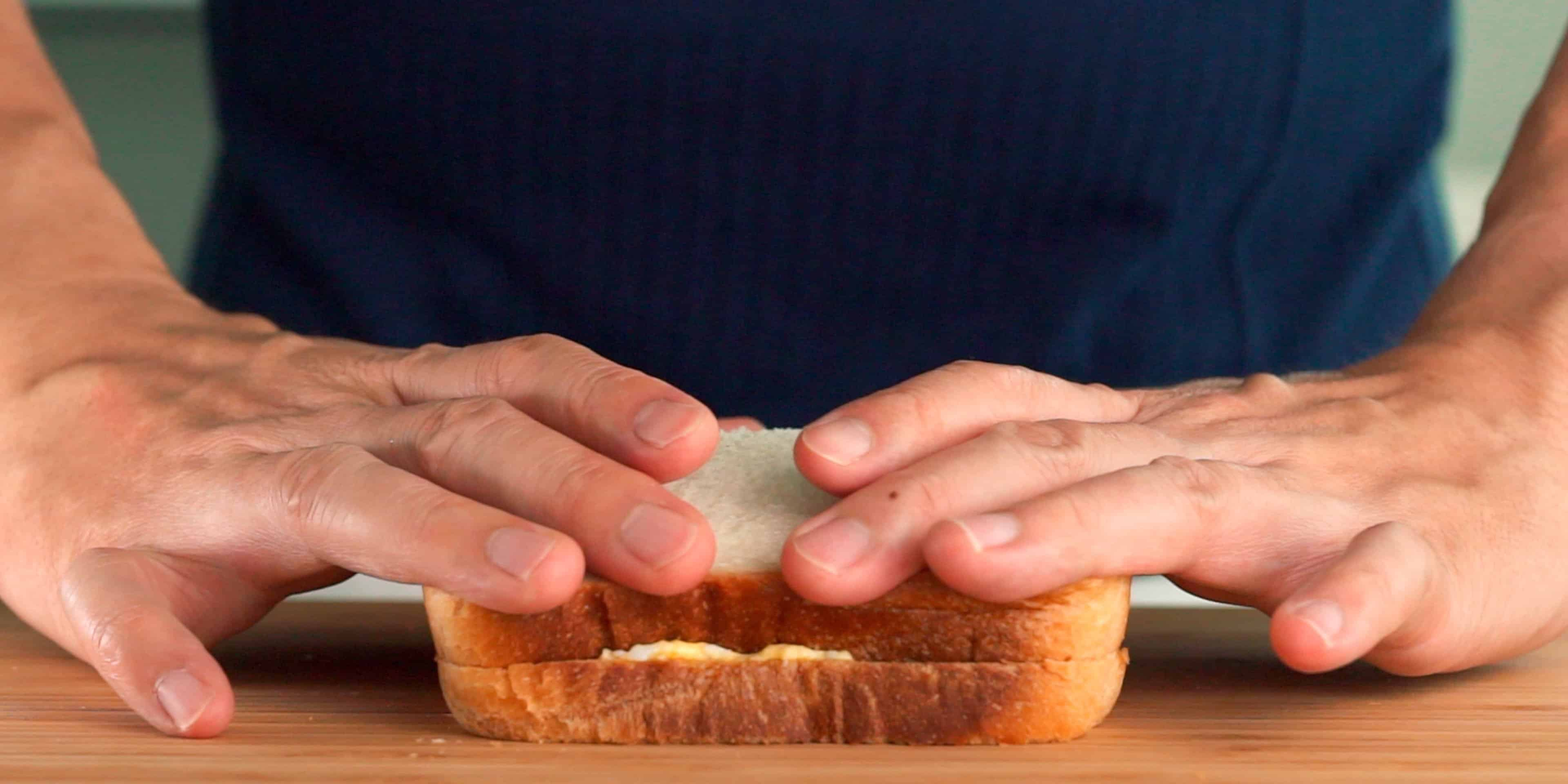 Smashing a Japanese style egg sandwich together.