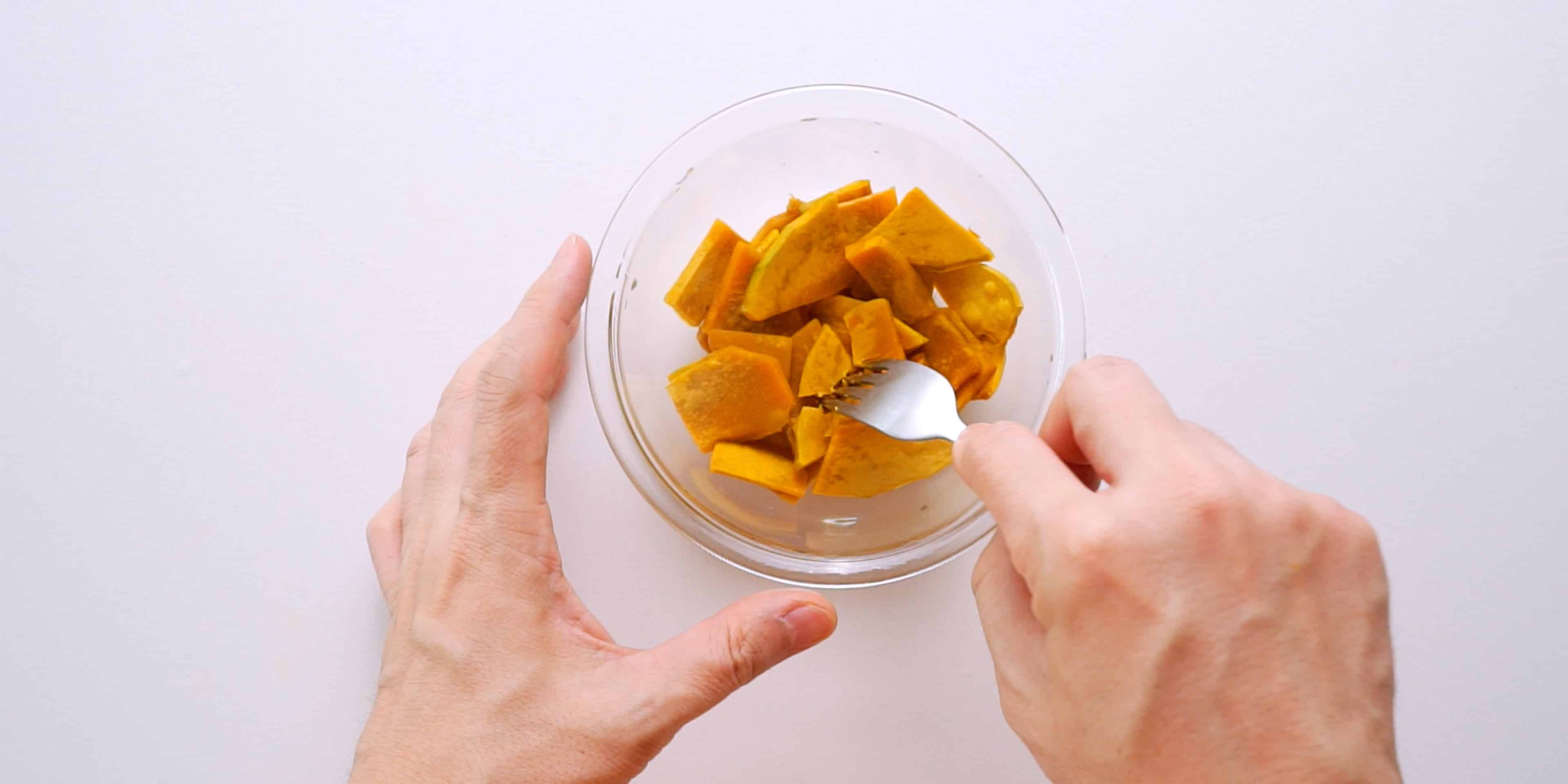 Testing steamed kabocha squash with a fork.