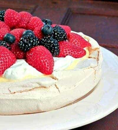 Pavlova with Lemon Curd   A meringue shell topped with lemon curd, cream and berries