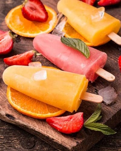Homemade refreshing fruit popsicle lollies on wooden table with berries and fruits