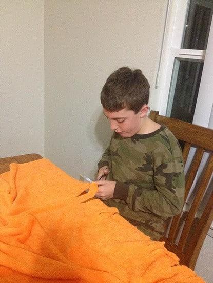 Jonathan (age 11) cuts his minkee fringe blanket
