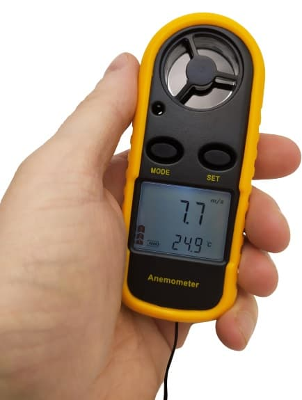 Image shows me holding the anemometer in my left hand with the LCD lit up.