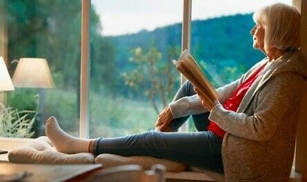 Frau liest am Fenster