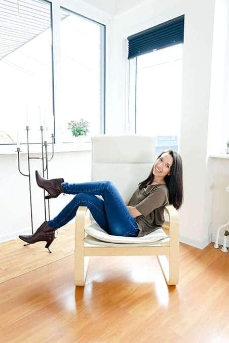 A brunette girl sitting and smiling in a chair
