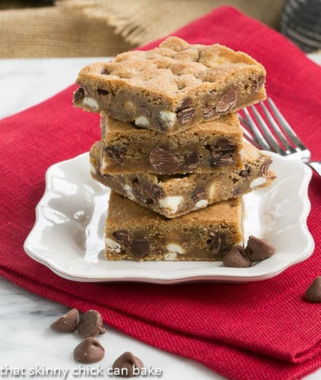 Chippy Bars AKA - Chocolate Chip Cookie Bars stacked on a square white plate with a fork
