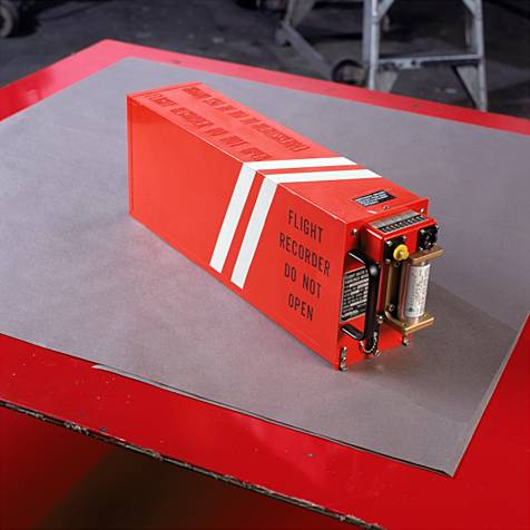 An orange Flight Recorder or black box rests on a table