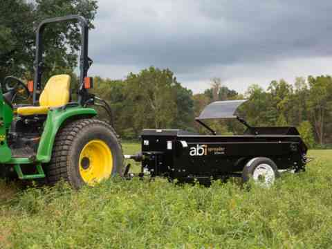 Small tractor 50 PTO manure and compost spreader in pasture