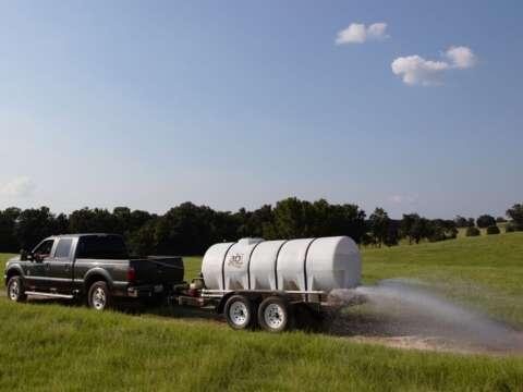 Truck 1000 Gallon Water Wagon Spraying Dirt Road