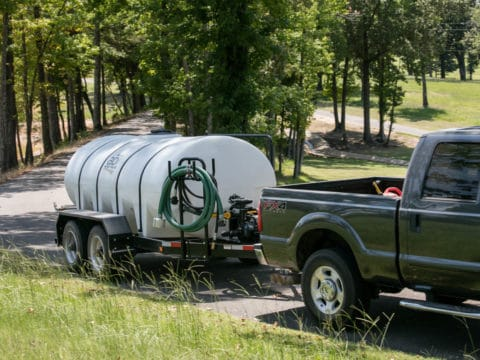 Truck Hauling 1600 D.O.T. Water Trailer On A Driveway