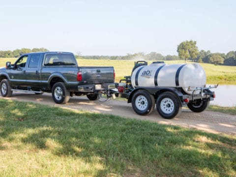 Truck Hauling 500 Gallon Water Trailer On A Dirt Road
