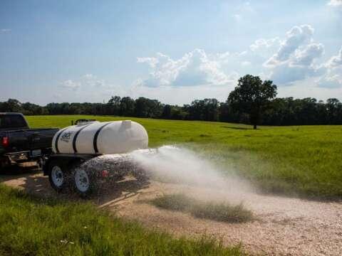 Truck 500 Gallon Water Trailer Spraying Dirt Road
