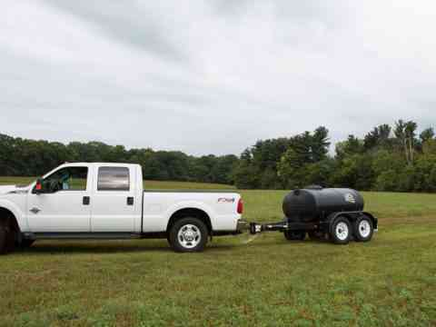 Truck Hauling Small Potable Water Trailer In A Pasture