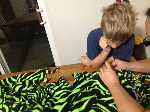 Caleb and Mommy tying no-sew fringe blanket
