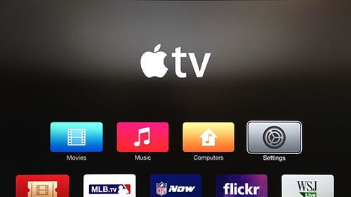 Apple TV screen with Settings button highlighted.