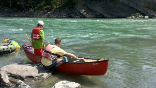 Putting canoes in the water for a camping adventure near banff