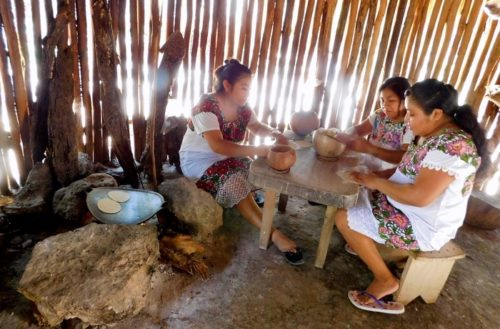 Women making tortillas by hand in a mayan village near coba