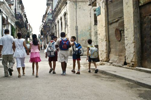 Kids, teens and parents explore a cuba city street.