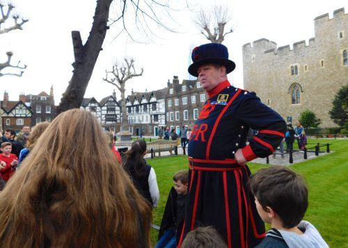 A beefeater entertain kids during a tower tour