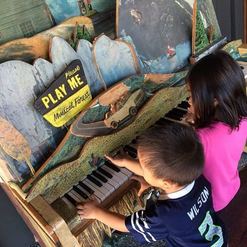 Kids playing together on a piano and bonding, one of the reasons to travel with kids