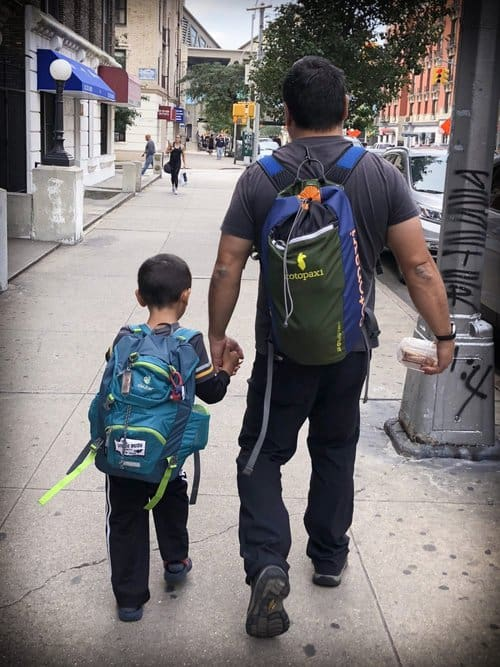 A young boy and his father walk through a New York City street, both carrying back packs. Visiting cities is one of many gap year ideas for traveling families.
