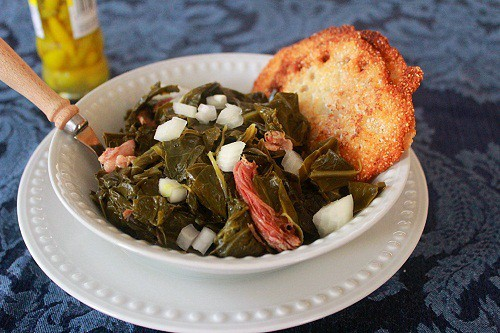 Collard Greens with ham hocks served with chopped onions, pepper vinegar and lacey cornbread