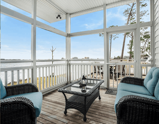 a bright screened in porch with a lake view at the Eagles Nest cabins in Gulf State Park