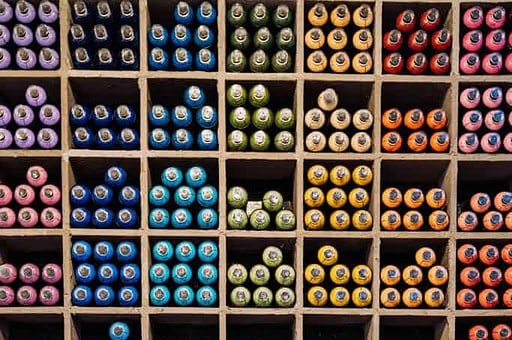 Organized shelves of different color threads