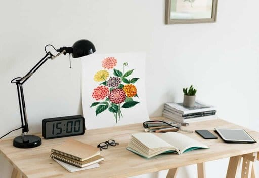 books and tablet on a desk with lamp