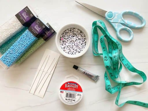 supplies for making braclets on a white table.
