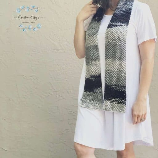 picture of woman in white dress with black grey ombre textured knit scarf on