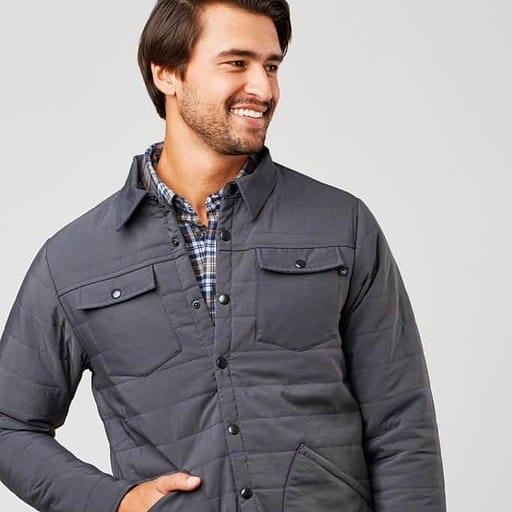 united by blue model wearing gray jacket with brown pants smiling