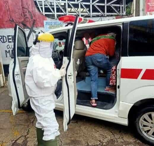 petugas medis covid-19 sedang mengevakuasi pasien