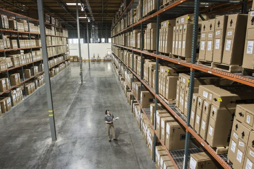 Warehouse worker checking inventory of stock on racks in a distribution warehouse.