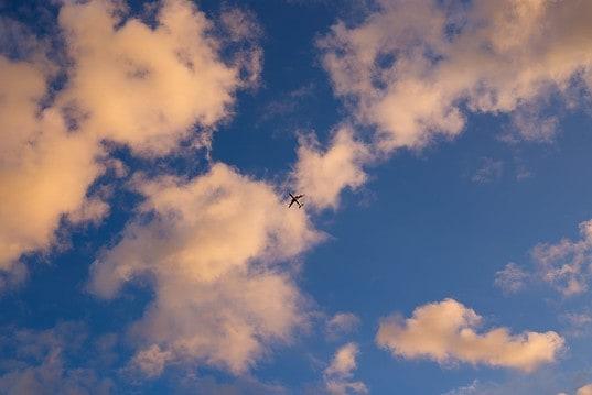 Photo by Jason Ortego on Unsplash. Plane, fly over, clouds, sky
