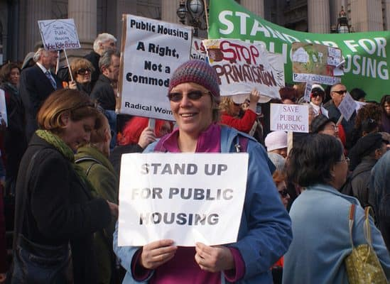 "Woman holding ""Stand up for public housing"" sign"