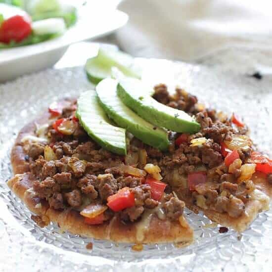 Cooked Ground Beef with Cheese and Sliced Avocados served on Pita bread pizza crust