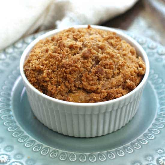 a coffee cake with streusel topping on a blue plate next to a white napkin.