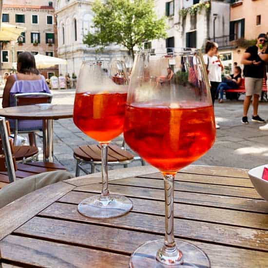 two glasses of Aperol Spritz on a wood table