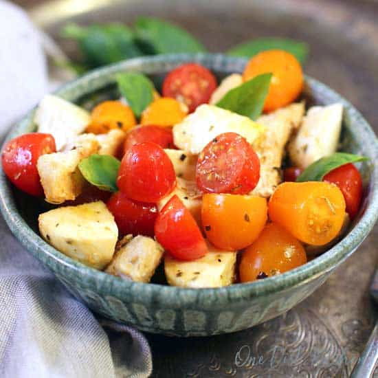 a bowl with chopped cherry tomatoes, chunks of mozzarella and cooked chicken.