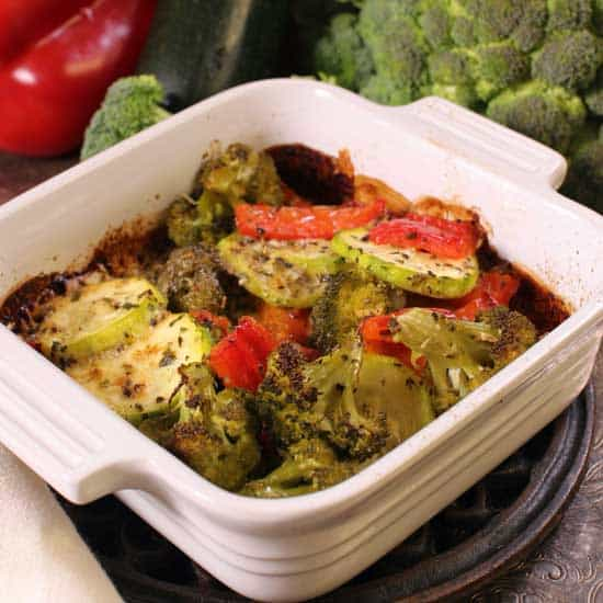 a vegetable casserole next to fresh peppers and broccoli.