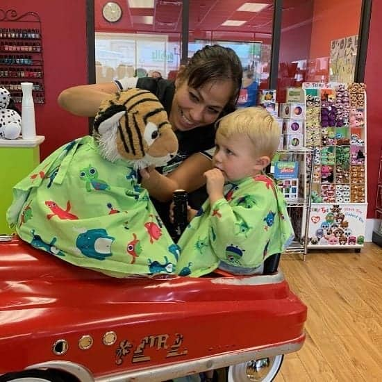 a stylist with a child at multi-unit franchisee Jennifer Tribble's salon