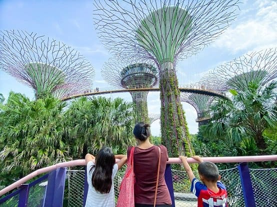 A mother and her daughter and son looking at the Gardens by the Bay in Singapore, raising her kids to be an avid traveller