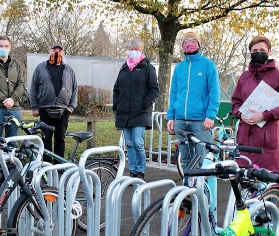 Sie freuen sich über die neuen Fahrradständer: Timo Roth (Energiemanager), Udo Thomsen (Hausmeister Grundschule Adelby), Inken Erichsen (Schulleiterin Grundschule Adelby), Till Fuder (Klimaschutzmanager), Simone Lange (Oberbürgermeisterin und Klimapakt-Vorstand) (v.l.n.r.)