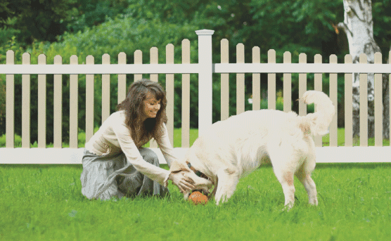 girl with dog in backyard by fence, happy that they have a fence