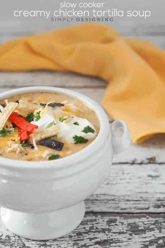 Creamy Chicken Tortilla Soup Slow Cooker Recipe topped with sour cream and tortilla strips in a white pedestal bowl with a yellow napkin behind it