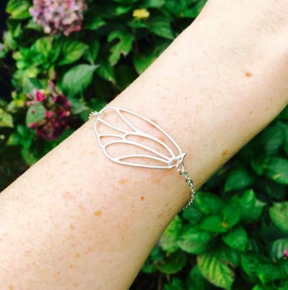 Silver butter fly bracelet on arm for sister maid of honor gift