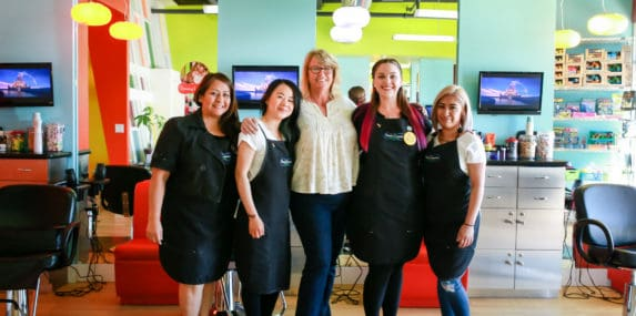pigtails & crewcuts franchisee with staff in kids' haircut franchise