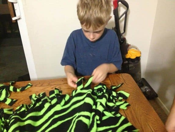 Looking for an easy craft for your kids to make?  A no-sew fringe blanket is perfect for kids at a pretty early age.  They will need a little help but essentially can do it themselves.