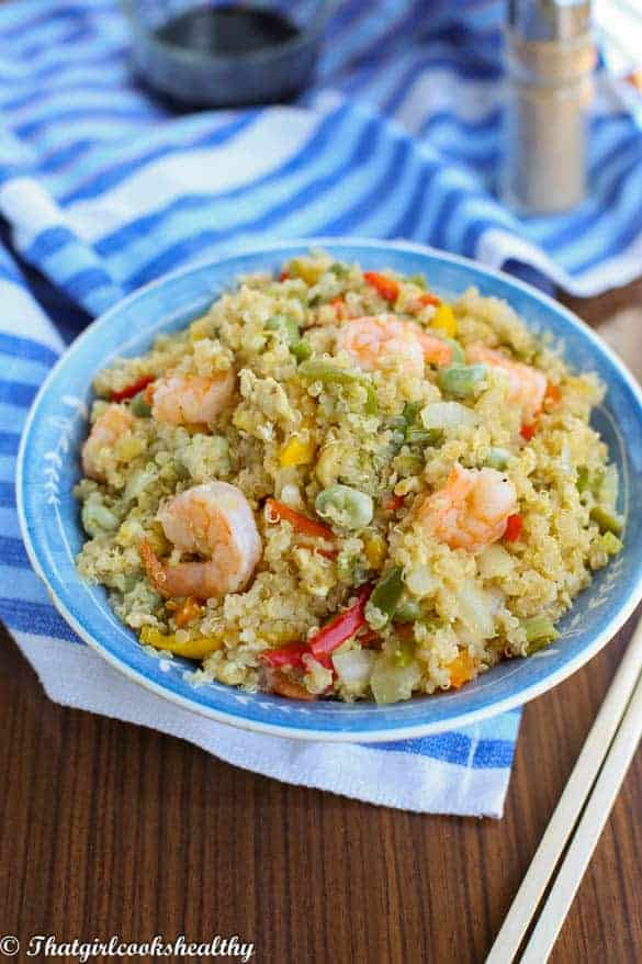 angle shot of shrimp and quinoa in a blue bowl