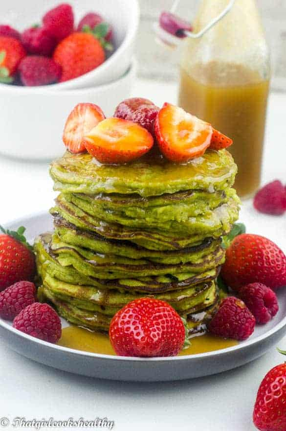 Gluten free spinach pancakes with fruit on plate
